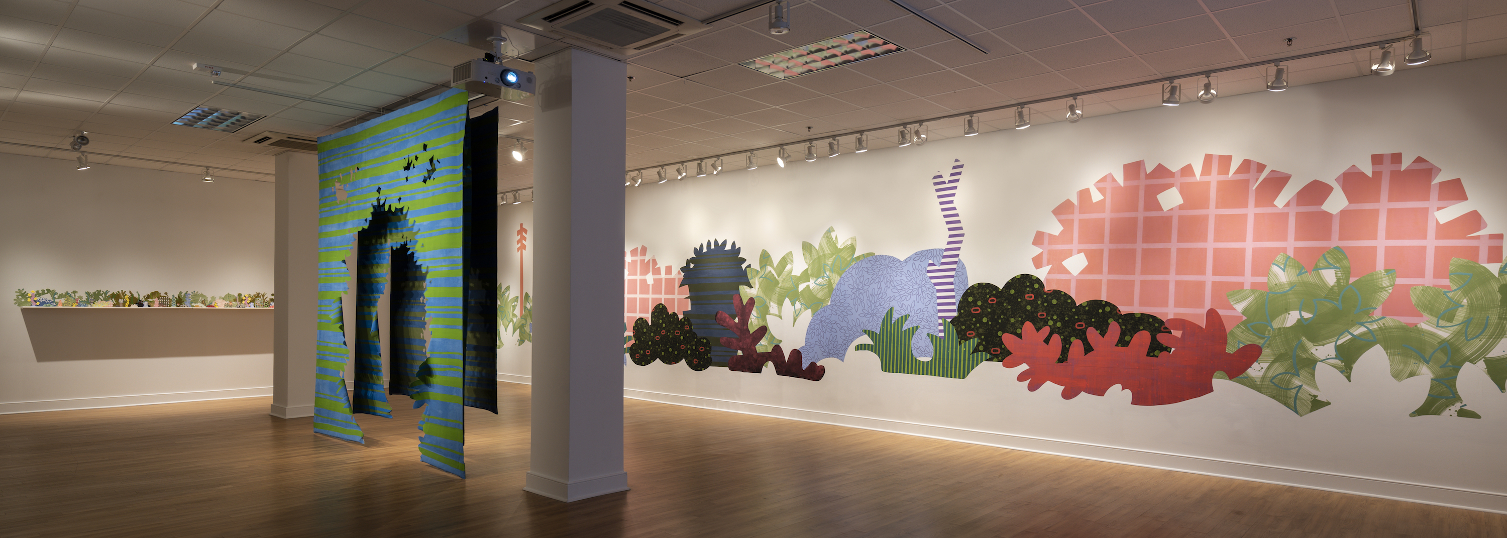 """Installation of """"Aggregate Optics of Make-A-Do"""" 2019; University of Memphis, Fogelman Galleries; From right to left: Piecemeal Promenade (2019) 48ft x 11ft; latex on muslin cut-outs, adhered to wall; Proscenium Hedgerow (2018) 11ft x 10ft x 2ft; series of three latex on cut muslin panels; Horizon Allsorts, (2018) 12ft x 1ft; (6) floating wood shelves, painted muslin, ceramic, underglaze and glaze"""