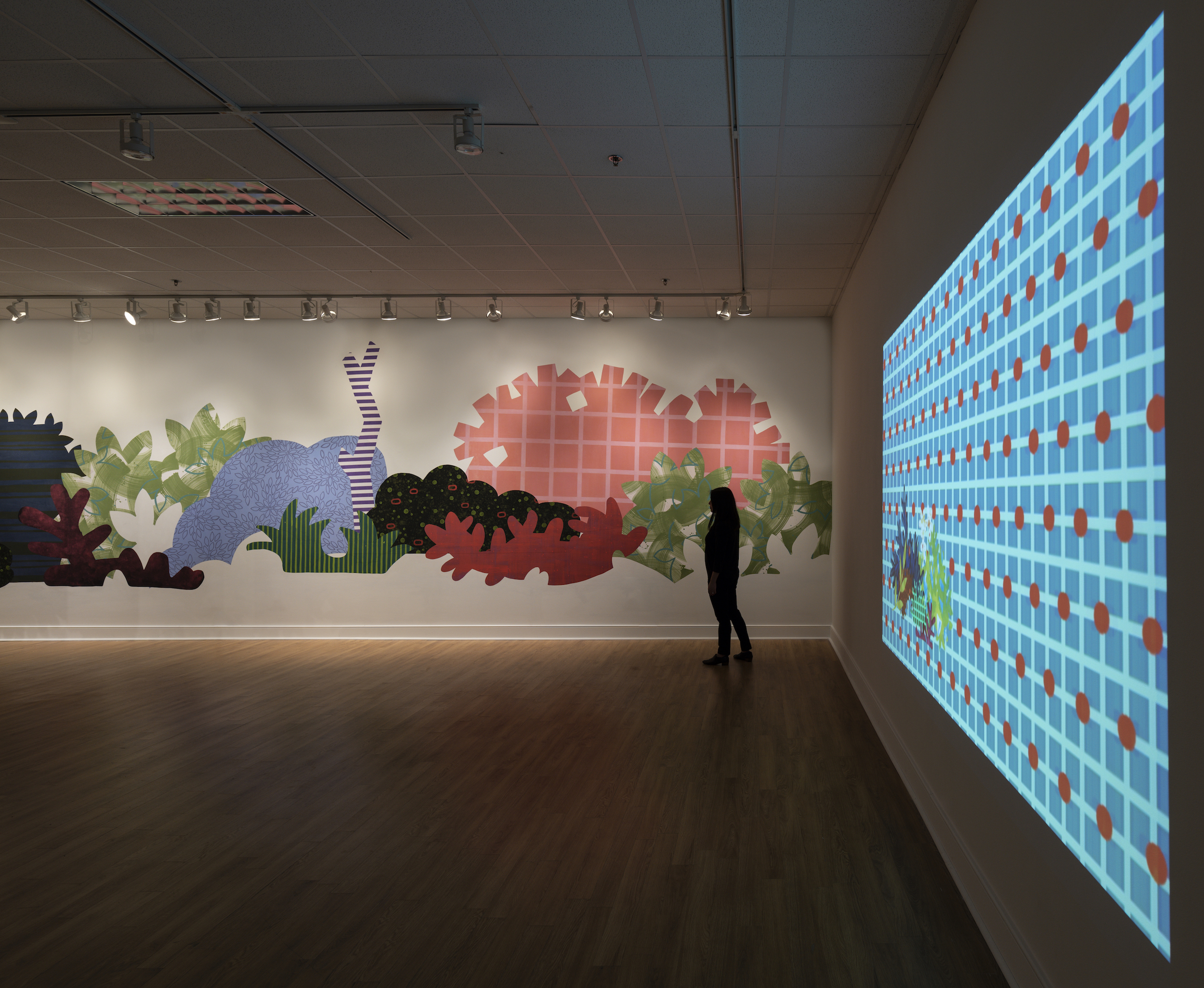 """Installation of """"Aggregate Optics of Make-A-Do"""" 2019; University of Memphis; Fogelman Galleries, Works from right to left: Blinky Bricolage (2019) 3 minute animation on loop, projection; Piecemeal Promenade (2019) 48ft x 11ft; latex on muslin cut-outs, adhered to wall"""